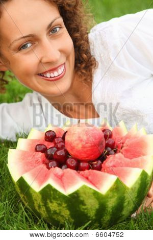 Young Beautiful Woman With Fruit Lying On A lawn