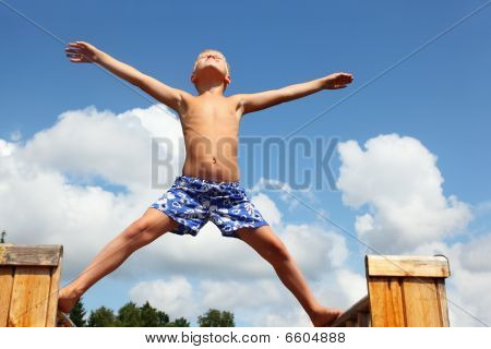 Boy In Shorts Standing On Boards Against Clouds, Plants Hands And Legs In Parties