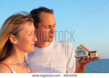 Young Woman And Man Keeping In Hands Model Of House With Garage Against Sea In Summer