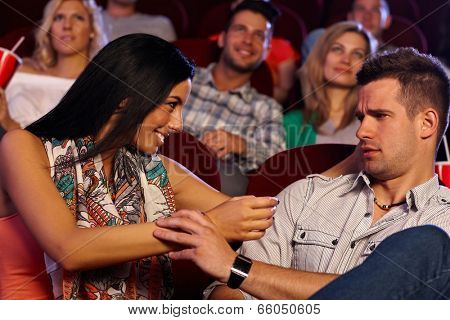 Pretty young woman molesting young man at movie theater.