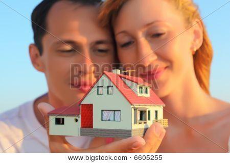 Joven mujer y hombre teniendo en manos modelo de casa con garaje