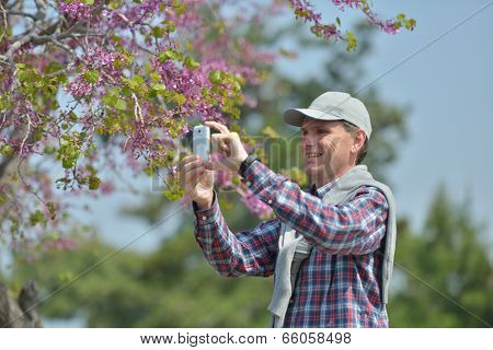 Mature man taking a picture using smartphone