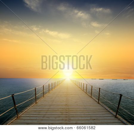 ocean sunrise with pier and beach in foreground