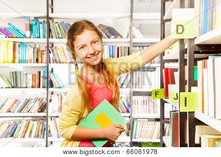 Smiling Girl With Two Braids Standing Near Shelf