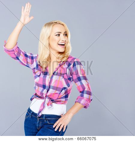 Beautiful young woman clowning around posing with on hand in the air and the other on her hip as she laughs and looks to the right of the frame  on grey with copyspace