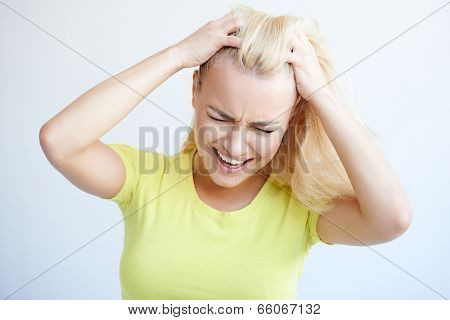 Angry woman tearing at her long blond her hair in frustration grimacing and frowning in desperation  isolated on grey