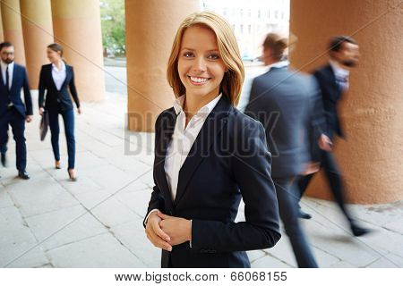Smiling businesswoman looking at camera with walking people on background