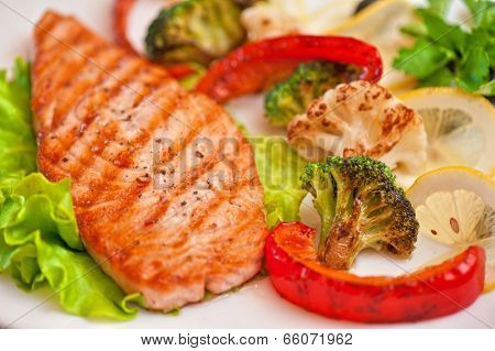 Tasty dish of salmon steak with vegetables