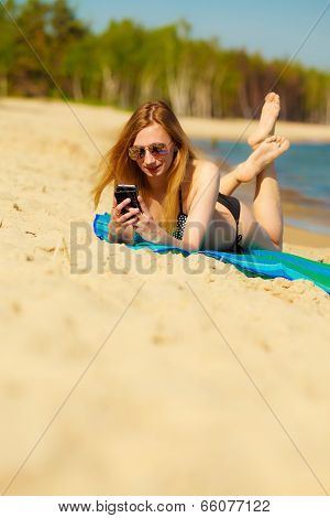 Girl With Phone Tanning On Beach
