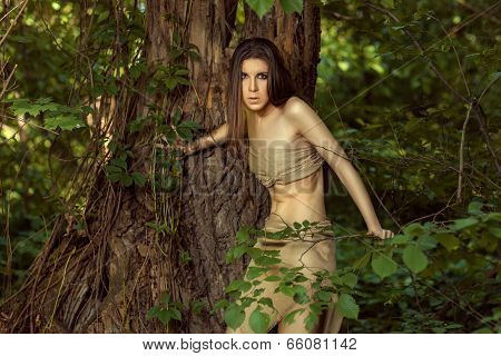 Savage Girl Looks Out From Behind A Tree.