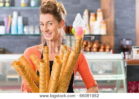 Young saleswoman in an ice cream parlor with many cones for ice cream cornets