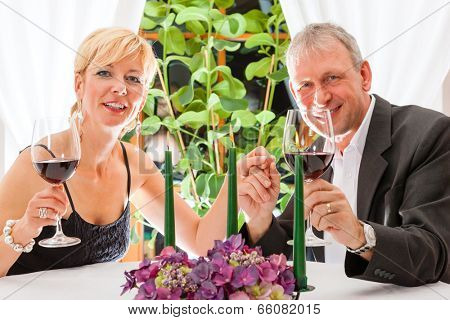 Senior couple having dinner in a restaurant, candles on the table, they are eating pasta