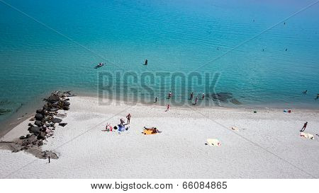 Top View Of Beach With Tourists, Sunbeds And Umbrellas. Sea Travel Destination. Holiday's Background
