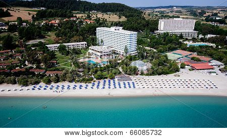 Top View Of Beach With Tourists, Sunbeds And Umbrellas At A Luxury Hotel. Sea Travel Destination.