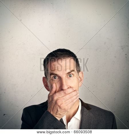 Businessman holding hand over his mouth