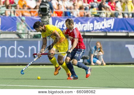 THE HAGUE, NETHERLANDS - JUNE 2: Englishman Catlin reaches for the ball, defending against by Indian player Rupinder  during the Hockey World Cup 2014. GBR beats IND 2-1