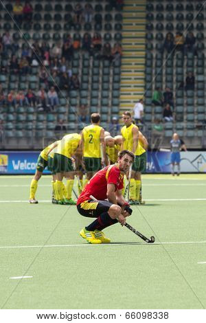 THE HAGUE, NETHERLANDS - JUNE 2 2014: Manel Terraza (Spain) squats down in disappointment after losing the match against Australia (huddling in the background) with 3-0 at the Rabobank World Cup Hockey