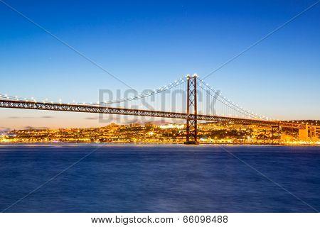 Lisbon cityscape and the 25 de Abril Bridge, Portugal at dusk