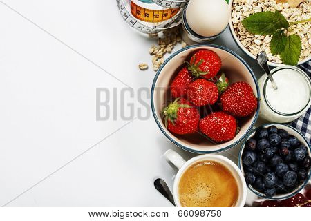 Healthy breakfast - yogurt, muesli, berries and measurement tape - health and diet concept