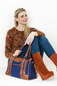 image of platform shoes  - sitting woman wearing fashionable platform brown shoes with a handbag - JPG