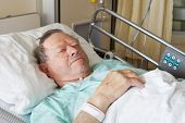 stock photo of intensive care unit  - Portrait of sick old man in hospital bed