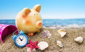 stock photo of sand dollar  - Piggy bank on sand with summer sea background - JPG