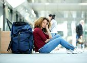 stock photo of sleeping bag  - Tired young woman sleeping at airport with luggage - JPG