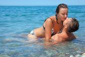 Постер, плакат: Молодая горячая женщина сидит верхом человек в море недалеко от побережья мужчина и женщина Kiss