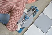 stock photo of tile  - Tiler cutting ceramic tiles during floor installation - JPG