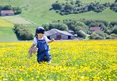 foto of dungarees  - A Baby Girl In Dungarees With A Soft Toy In Her Hands Walking In The Field Full Of Buttercups - JPG