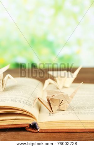 Origami cranes on old book on wooden table, outdoors
