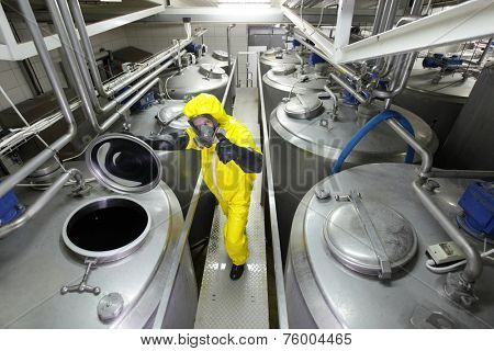 Technician in protective uniform,mask,and gloves controlling industrial process with thumb up gesture