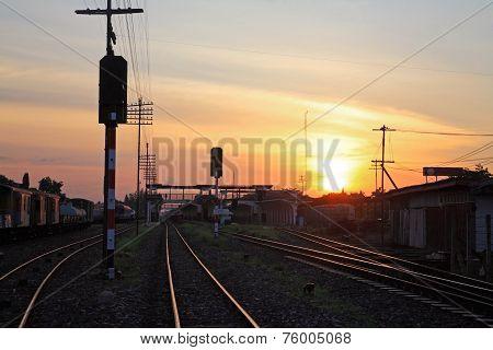 Railway Tracks At Train Station At Sunset