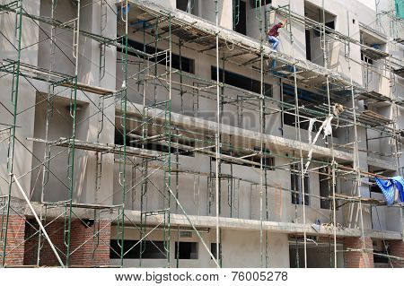 Worker On Iron Scaffolding At Construction Site