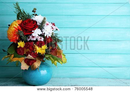Flower bouquet in blue vase on table on blue wooden wall background