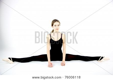 Serious Female Dancer Doing Split On The Ground Isolated