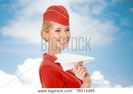 Charming Stewardess Holding Paper Plane In Hand. Sky With Clouds Background.