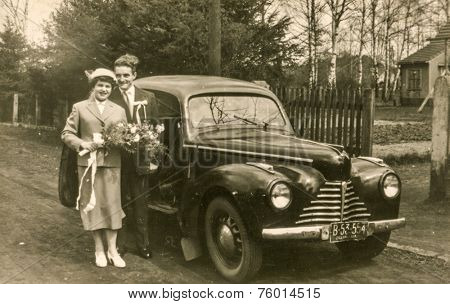 ILOWA ZAGANSKA, POLAND, CIRCA FIFTIES: Vintage photo of newlyweds with an old car