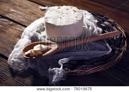Cottage cheese and butter in spoon on gauze on wicker mat on wooden background