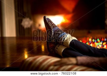 Portrait Of Feet At Woolen Socks Warming At Fireplace In Winter