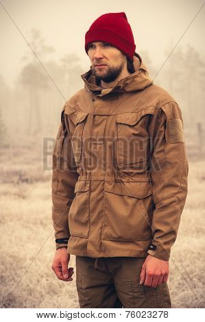 Young Man wearing winter hat clothing outdoor with foggy nature on background