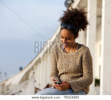 Young Woman Smiling Outdoors With Mobile Phone And Earphones