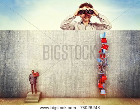 man with binoculars and worker behind the wall