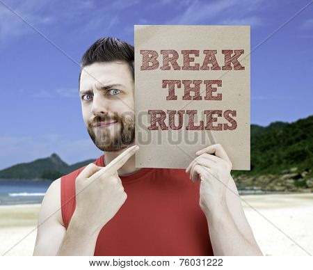 Man holding a card with the text Break The Rules on a beach background