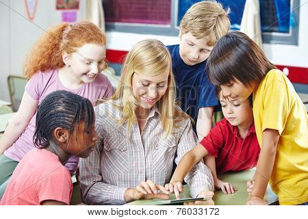 Teacher and students with tablet computer in elementary school class