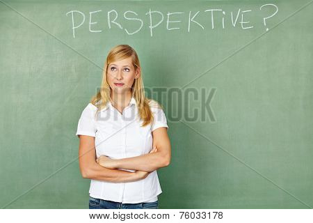 Woman in front of chalkboard thinking with German word for