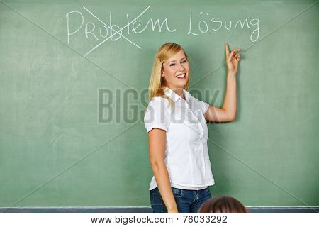 Happy woman pointing to German words for problem and solution on chalkboard