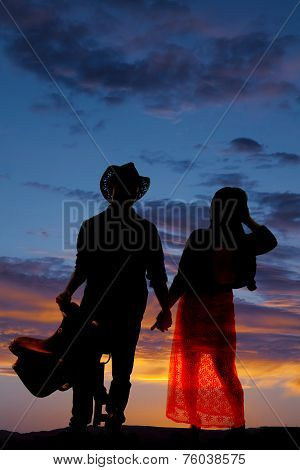 a silhouette of a cowboy holding on to his saddle and his woman