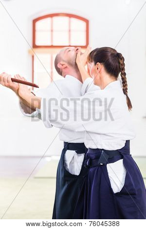 Man and woman fighting with wooden knifes at Aikido training in martial arts school