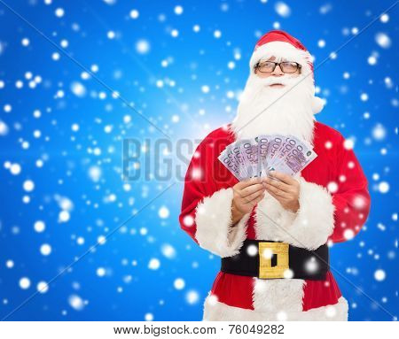 christmas, holidays, winning, currency and people concept - man in costume of santa claus with euro money over blue snowy background